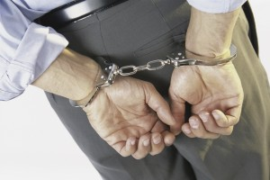 Close-up of a businessman with his hands handcuffed behind his back